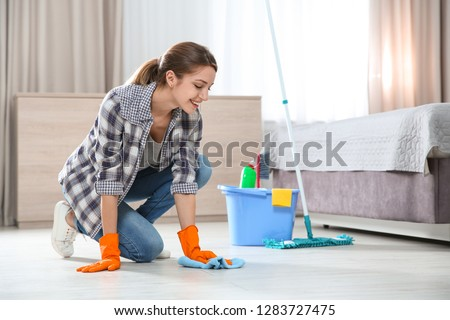 Young woman washing floor with rag and detergent in bedroom. Cleaning service #1283727475