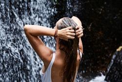 Young woman washing hair in waterfall, rear view