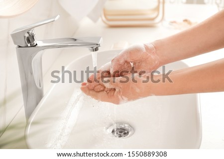 Young woman washing hands with soap over sink in bathroom, closeup