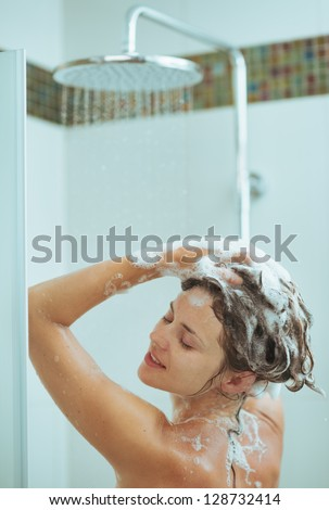 Young woman washing head with shampoo