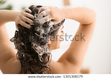 Young woman washing her beautiful hair in bathroom