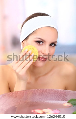 Young woman washing her face. Conceptual photo: make-up remover