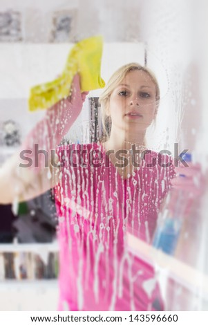 Young woman washing the window glass.