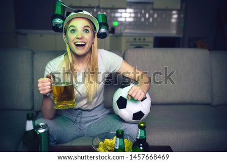 Young woman watch football game on tv at night. Cheerful attractive blonde woman hold glass of beer and ball. Bottles on table. Cheering. Alone in room.