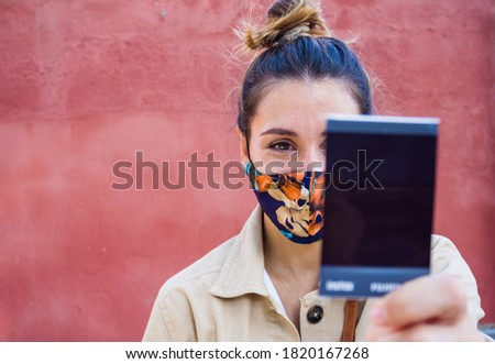 Young woman watching an instax photo with a flowers mask with a red wall on the background. Zdjęcia stock ©