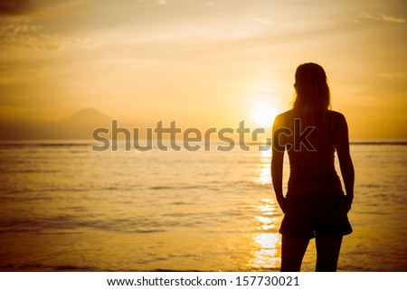Young woman watching as sun sets over Bali island