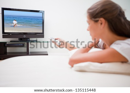 Young woman watching television in the living room