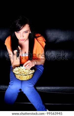 Young woman watching TV, eating popcorn