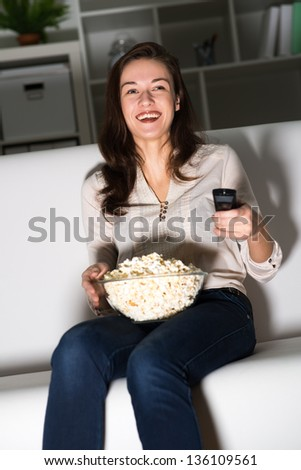 Young woman watching TV on the couch, eating popcorn