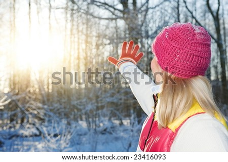 Young woman waving goodbye to winter