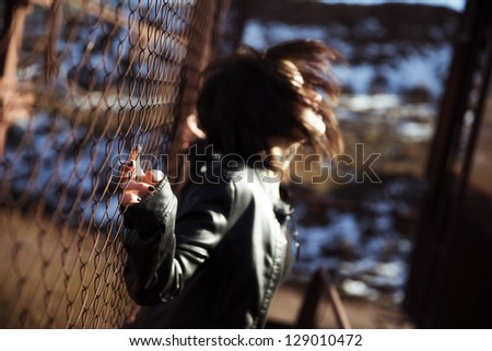 Young woman waving her hair on urban blurry environment