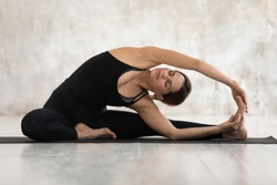 Young woman wear black sportswear practising yoga on mat, european female doing Revolved Head to Knee Forward exercise Parivrtta Janu Sirsasana pose, working out indoors mental physical health concept