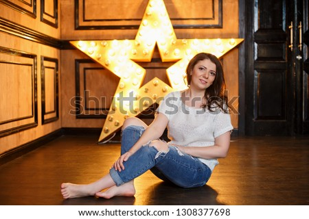 Young woman weared in casual on background of lighting star. Cheerful woman. New Year or Christmas mood. Young girl indoor seat on background of lighting star.  #1308377698