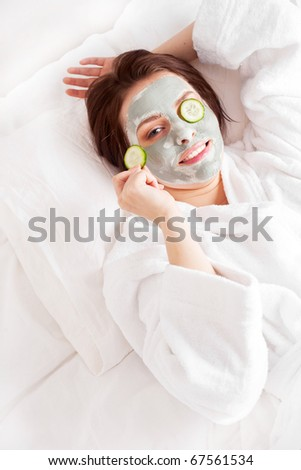 young woman wearing a deep cleansing green clay mask on her face and cucumbers on her eyes