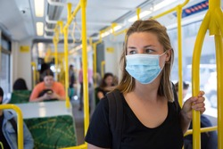 Young Woman Wearing a Face Mask Riding Public Transport