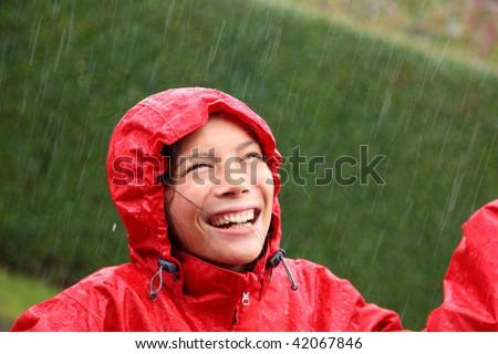 Young woman wearing a red raincoat enjoying the rain and having fun outside.