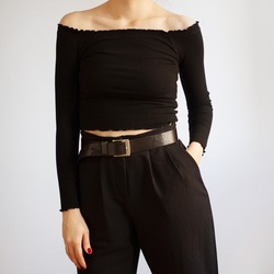 Young woman wearing all black outfit with off shoulder top and black high-waisted trousers isolated on white background.