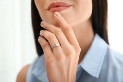 Young woman wearing beautiful engagement ring, closeup