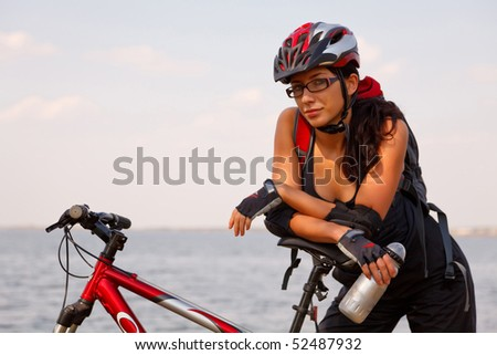 Young woman wearing bicycle helmet,standing by bicycle, holding water bottle.