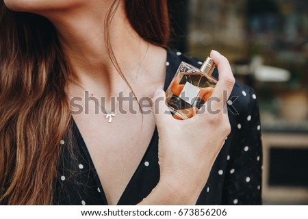 young woman wearing black and white polka dot dress posing with a bottle of expensive perfume. beautiful and stylish european fashion blogger posing with perfume outdoors. perfect summer outfit.