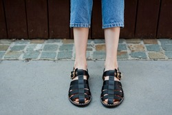 Young woman wearing black satin fisherman sandals. Street style.