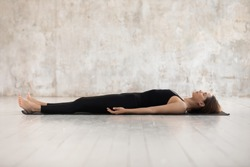 Young woman wearing black sportswear practicing yoga, doing Corpse, Savasana exercise, relaxing, lying in Dead Body pose on mat, sporty girl working out at home or in yoga studio with grey walls