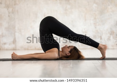 Young woman wearing black sportswear practicing yoga, doing Halasana exercise, standing in Plough pose, beautiful sporty girl with closed eyes working out at home or in yoga studio with grey walls Сток-фото ©