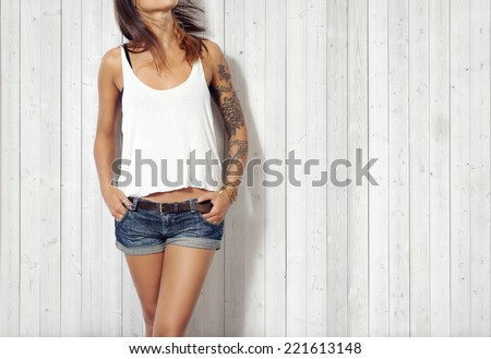 Young woman wearing blank vest. Wood wall background.