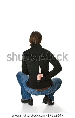 Young woman wearing blue jeans and a black jacket crouches and holds a knife behind her back. Isolated on a white background.