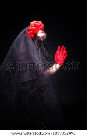 Young woman wearing bridal veil, sugar skull makeup and rose headpiece praying; concept of Halloween or Día de Muertos (Day of the Dead) celebration; isolated on black background Foto d'archivio ©