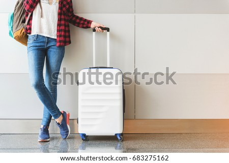 Young woman wearing casual clothes is posing at airport