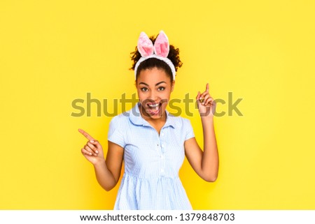 7a97569f8eaf Young woman wearing cute dress and bunny ears headband standing isolated on  yellow background dancing pointing