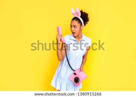 0614c2cbd9d8 Young woman wearing cute dress and bunny ears headband standing isolated on  yellow background holding stationary