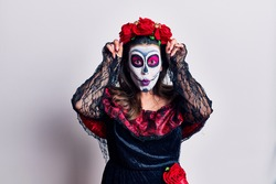 Young woman wearing day of the dead costume over white doing funny gesture with finger over head as bull horns