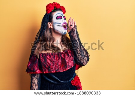 Young woman wearing day of the dead costume over yellow shouting and screaming loud to side with hand on mouth. communication concept.  Foto stock ©