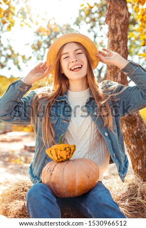 Young woman wearing denim outfit sitting at garden outdoors holding pumpkin harvest preparing for halloween holding hat posing to ca,era laughing happy Zdjęcia stock ©