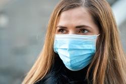 Young woman wearing disposable blue virus face mouth nose mask, closeup portrait. Coronavirus covid-19 outbreak prevention concept