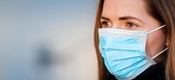 Young woman wearing disposable blue virus face mouth nose mask, closeup portrait - wide banner with space for text left side. Coronavirus covid-19 outbreak prevention concept