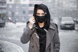 Young woman wearing face mask. Handsome woman in black hoodie wear black medical mask. Pandemic coronavirus covid-19 quarantine period concept.