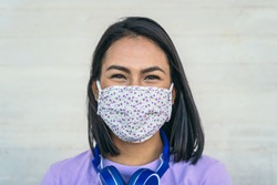 Young woman wearing face mask portrait - Latin girl using protective facemask for preventing spread of corona virus - Health care and pandemic crisis concept