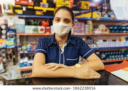 Young woman wearing face mask working in hardware store ストックフォト ©