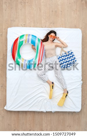 Young woman wearing flippers and sunglasses lying on bed bedtime top view holding swim ring and beach bag posing to camera smiling happy