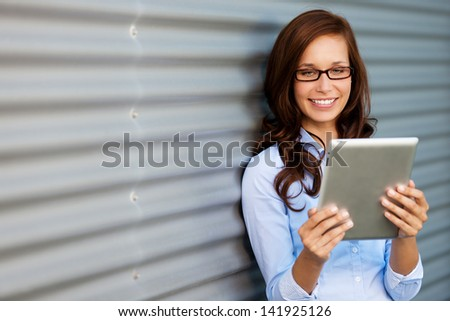 Young woman wearing glasses leaning against a corrugated metal wall or door reading her tablet computer, angled with copyspace