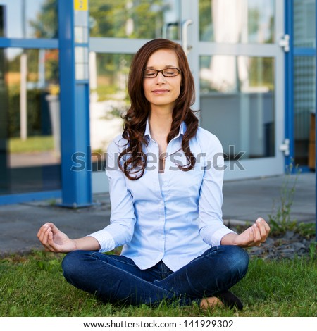 Young woman wearing glasses with a serene expression sitting meditating on green grass in front of a commercial building or college