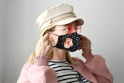 Young woman wearing handmade stylish cloth cotton face mask as decorative accessory element. Popular trend in fashion industry. Reusable face mask.