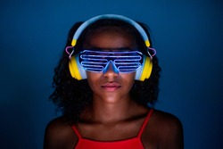 Young woman wearing headphones and futuristic led glasses on blue background - Isolated black woman wearing 3d smart glasses and headphones - virtual reality, future, technology concept