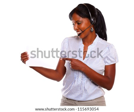 Young woman wearing headphones holding a white card on isolated background - copyspace