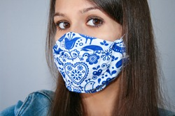Young Woman Wearing Home Made, Protective, Face Mask. Self Isolation, Quarantine, Protection against Covid 19, Corona Virus. Close up at home.