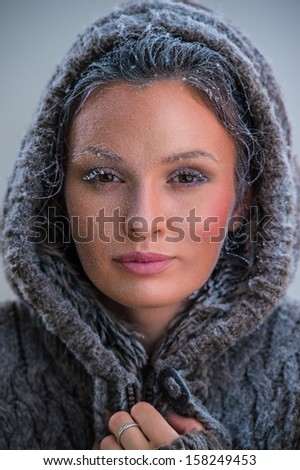 Young woman wearing hoodie warming after cooling in snow. Frost makeup #158249453