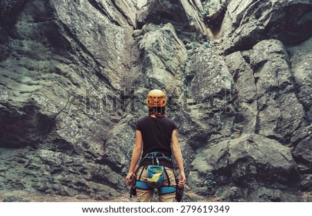Young woman wearing in climbing equipment standing in front of a stone rock outdoor and preparing to climb, rear view ストックフォト ©